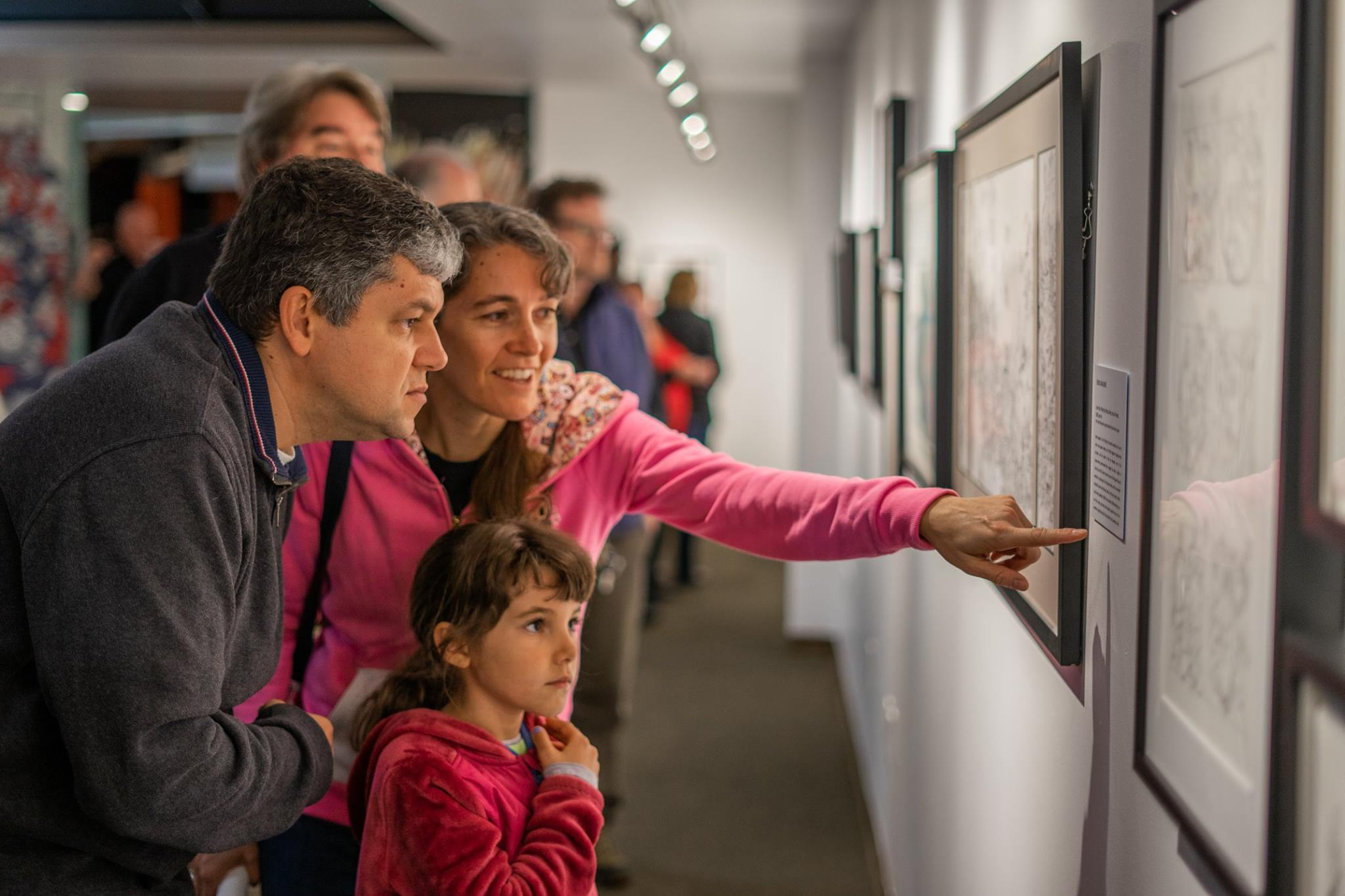 Family looking at Cover Story exhibit